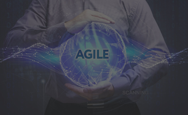 Young businessman shows the word: Agile